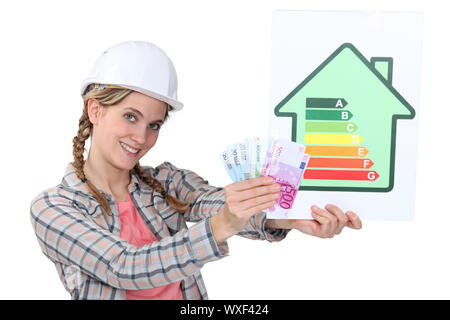 Construction worker with cash and an energy rating card - Stock Photo