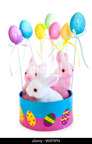 Cute Easter bunny toys in basket with balloons isolated on white background - Stock Photo