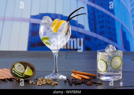 Gin tonic cocktail with spices in urban city buildings background - Stock Photo