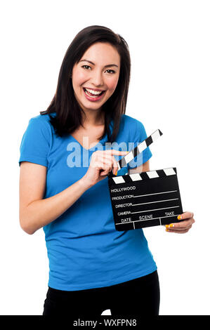 Cheerful asian young female holding clapperboard over white