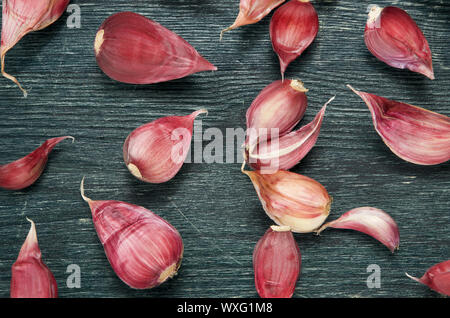 Vegetables background. Fresh garlic on a dark embossed surface. View from above. - Stock Photo