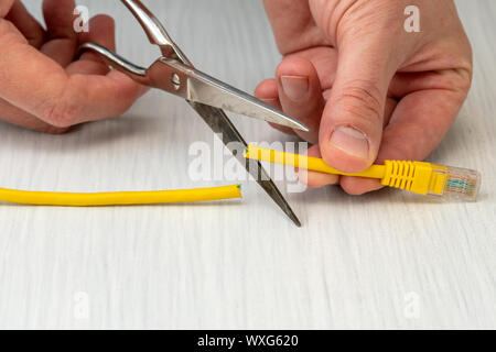 Internet censor cutting a yellow network cable with scissors.Restricted internet access concept - Stock Photo