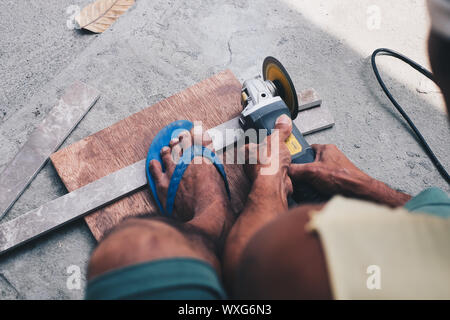 Working man cutting metal bar with circular saw. High angle view. - Stock Photo