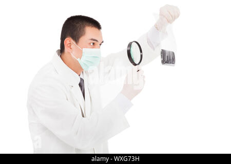 young investigator watching the evidence by magnifier - Stock Photo