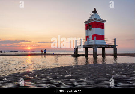 Lighthouse at sunset in Italy with beach Stock Photo