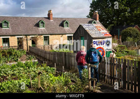 UK, County Durham, Beamish, Museum, Pit Village, Francis Street, visitors in miner's cottage vegetable gardens at hut made from old enamel advertising - Stock Photo