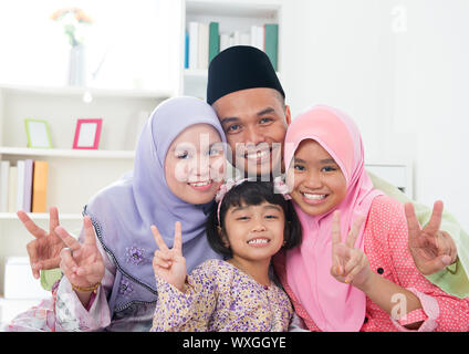Happy Asian family at home. Muslim family showing v victory hand sign and having fun. Southeast Asian parents and children smiling. - Stock Photo