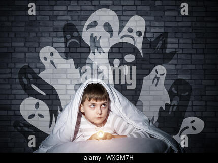 Frightened child with flashlight hiding under blanket. Halloween scary ghostly monsters on wall. Scared kid in pajamas lying in his bed at home. Fear