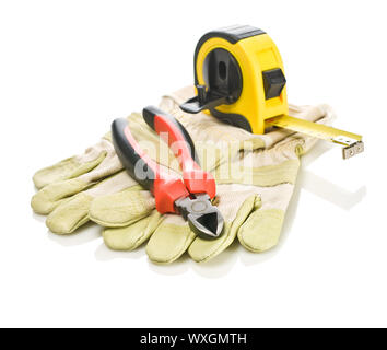 pliers and tapeline on gloves - Stock Photo