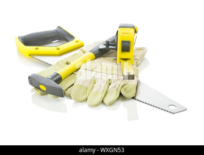 tapeline, hammer and gloves on saw - Stock Photo