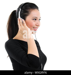 Telemarketing headset woman in black suit from call center smiling happy talking in hands free headset device. Attractive mixed race Southeast Asian / - Stock Photo