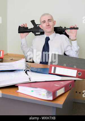 The self-satisfied worker of office armed with a rifle - Stock Photo