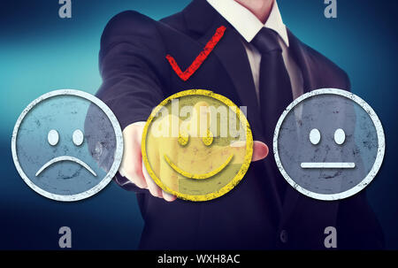 Business man pointing a yellow smiley face - Stock Photo