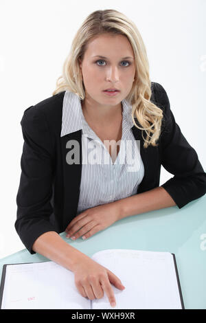 Blond woman checking diary for free appointments - Stock Photo