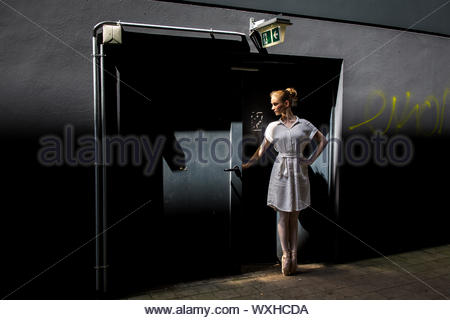 Contemporary female dancer wearing white performing on the street in front of an industrial door - Stock Photo