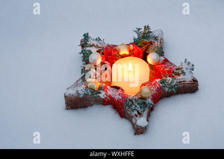 Christmas wreath: A Christmas-decorated wreath with a burning golden candle hangs on a wooden wall, Switzerland - Stock Photo