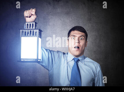 Horrified businessman holding glowing lantern on background grunge wall. Young emotional corporate employee in shirt and tie looking for something at - Stock Photo