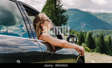 Happy woman travels by car in the mountains. Summer vacation concept. Woman out the window enjoying mountain view