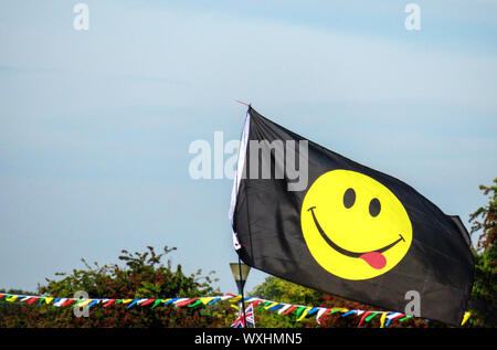Yellow Smiling Face emoji on a black flag - Stock Photo