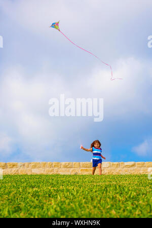 Sweet little girl running with kite on green field, adorable child having fun on backyard, playing game with windy paper toy outdoors, happiness conce - Stock Photo