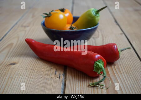 Set of multicolored sweet peppers and yellow heirloom tomatoes in a blue ceramic bowl on a rustic wooden table - Stock Photo