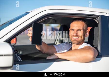 An attractive man in a car shows a smartphone. - Stock Photo