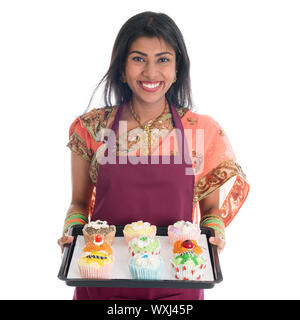Traditional Indian woman in sari baking bread and cupcakes, wearing apron holding tray isolated on white. - Stock Photo