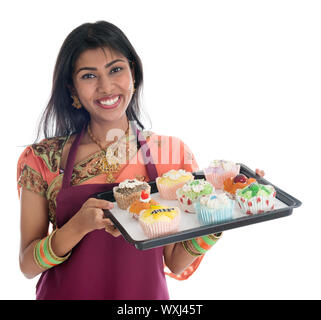 Happy Traditional Indian woman in sari baking bread and cupcakes, wearing apron holding tray isolated on white. - Stock Photo