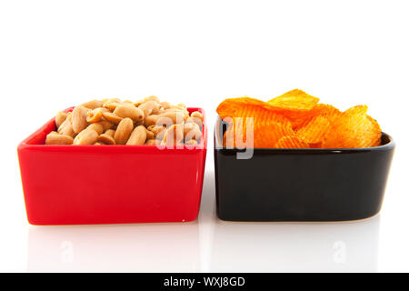 Peanuts and potato chips in red and black  bowls - Stock Photo