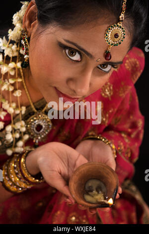 Close up portrait of beautiful young Indian woman in traditional sari dress holding a diwali oil lamp light, isolated on black background. - Stock Photo