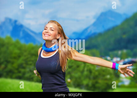 Portrait of happy traveler girl with raised up hands enjoying sunny day, mountains landscape, travel to Europe, happiness emotion, summer holiday conc - Stock Photo