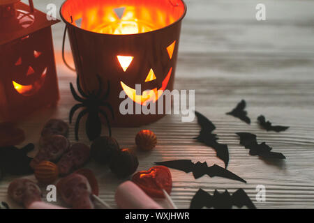 Glowing jack o lantern face, festive candy, skulls, black bats, ghost, spider decorations on white wooden background in dark. Happy Halloween. Copy sp - Stock Photo