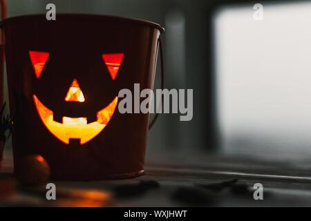 Glowing Jack-o-lantern head in dark. Happy Halloween. Jack o lantern glowing face pumpkin on black background. Trick or treat. Copy space - Stock Photo
