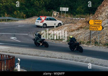 Motorcyclists on mountainous road, enjoying tour along summertime activities, wonderful mountai - Stock Photo