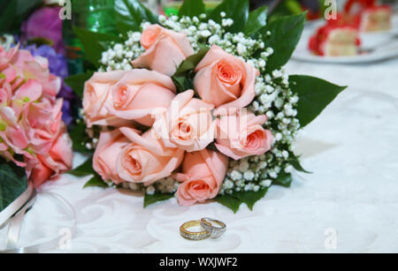 Gold wedding rings on the pink bouquet of flowers . Stylish pink engagement flower Rings in front of the wedding bouquet . - Stock Photo