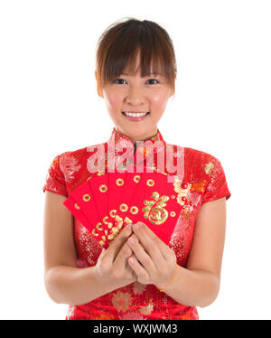 Pretty Asian woman with Chinese traditional dress cheongsam or qipao holding ang pow or red packet monetary gift. Chinese new year concept, female mod - Stock Photo