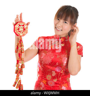 Pretty Asian woman with Chinese traditional dress cheongsam or qipao holding fire crackers. Chinese new year concept, the Chinese words means prosperi - Stock Photo