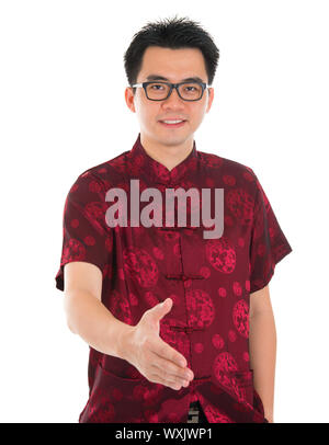 Asian man in traditional Chinese Cheongsam or Tang suit extending hand to give a handshake, standing isolated on white background. Asian male model. - Stock Photo