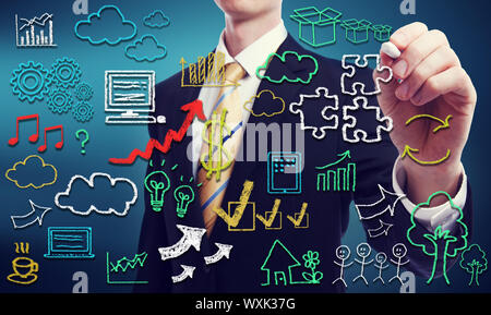 Businessman with hand written cloud computing themed texts and pictures - Stock Photo