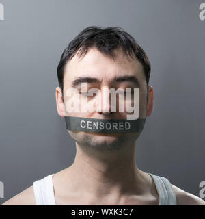 man's portrait with bandage on his face which represents censorship of statements - Stock Photo