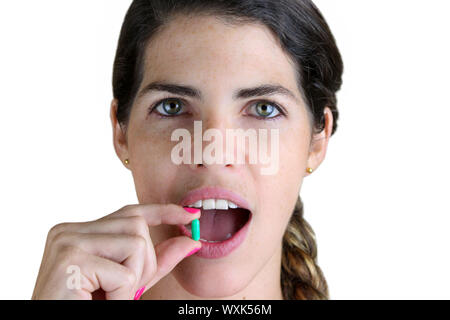 Young Woman taking a green pill - Stock Photo