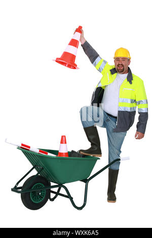Traffic worker with cone and wheelbarrow - Stock Photo