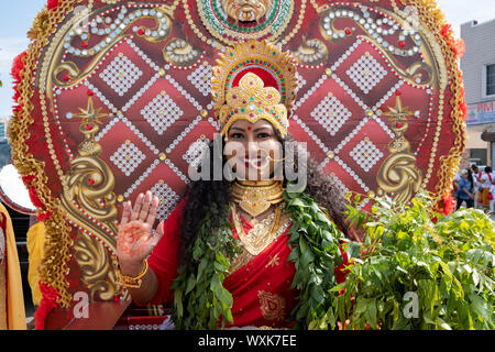 A beautiful Hindu woman with long curly hait dressed as the Goddess Mariamma the Madrassi Parade for unity in the community in Richmond Hill, Queens. - Stock Photo