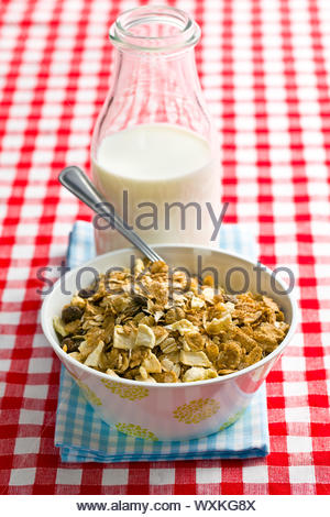 muesli and milk on checkered tablecloth - Stock Photo