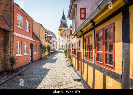 An alleyway with cobblestones and half timbered houses, leading up to the church in Faaborg, Denmark, July 12, 2019 Stock Photo