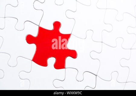 White jigsaw puzzle with one highlighted red piece - Stock Photo