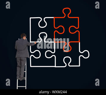 Businessman on a ladder drawing jigsaw puzzle on black background - Stock Photo