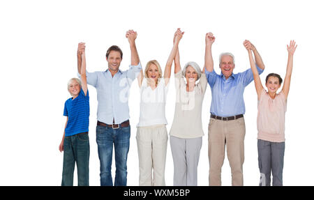 Smiling family raising their arms against white background - Stock Photo