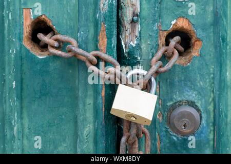 Padlock and chain on an old door, illustrating concepts of security and encryption - Stock Photo