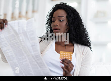 Shocked african american woman reading leaflet before taking contraceptive pills